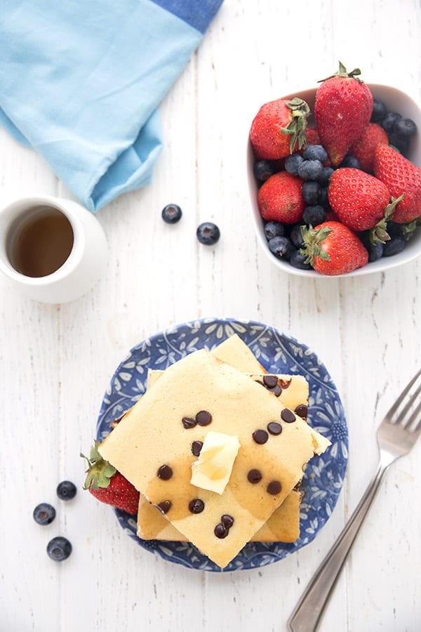 Baked keto pancakes on a white table with berries and a blue napkin