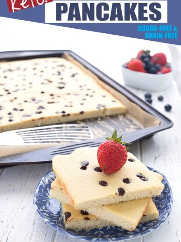 A stack of sheet pan pancakes on a blue plate with a strawberry