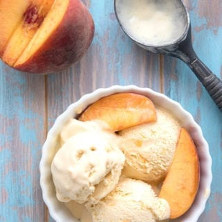 Top down photo of peach ice cream in a white bowl on a blue weathered table.