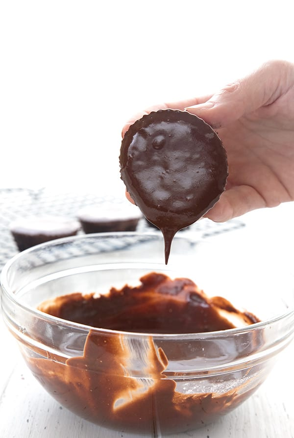 A keto brownie cupcake being dipped into chocolate peanut butter glaze