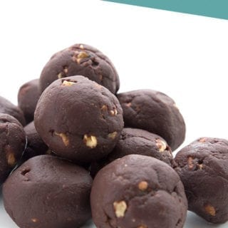 Keto chocolate fat bombs in a pile on a white background
