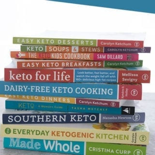 A pile of the best keto cookbooks, spines and titles facing outward