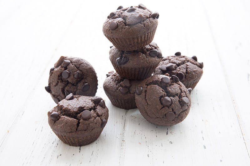 Double chocolate mini muffins in a pile on a white table
