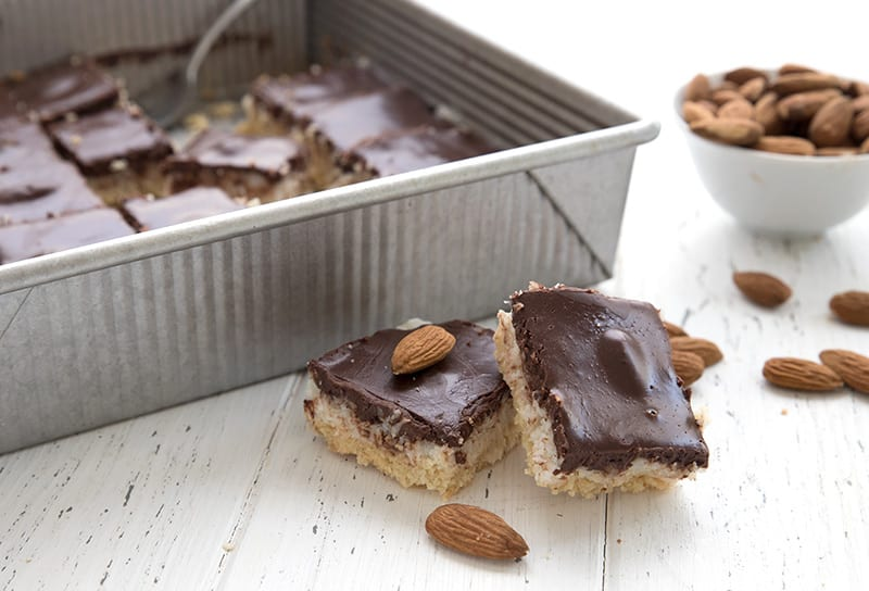 Two almond joy bars on a white table with almonds scattered around and the pan of bars in behind.