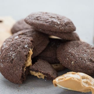 A stack of keto chocolate peanut butter cookies with a scoop of peanut butter in front