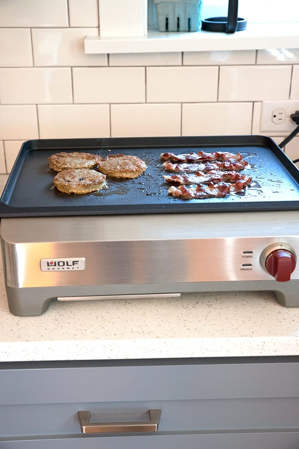 Countertop griddle with bacon and sausage being cooked on top