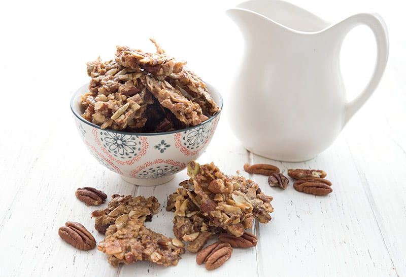 Low carb granola in a bowl with a white pitcher