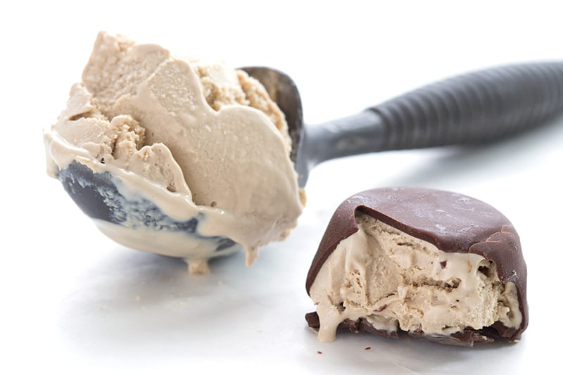 A scoop of coffee ice cream beside a chocolate covered ice cream truffle