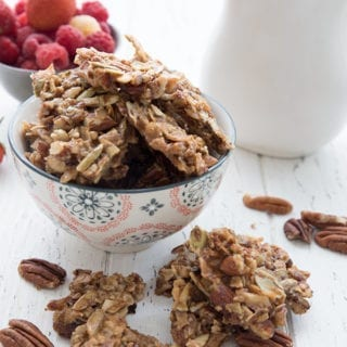 A bowl of granola clusters with berries in the background