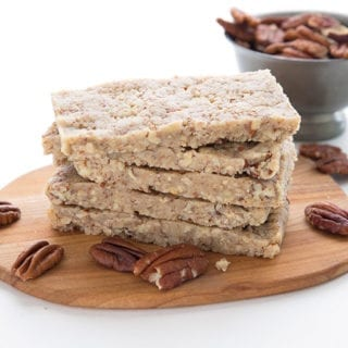 Keto pecan pie protein bars in a stack on a small cutting board