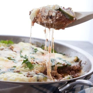 A scoopful of keto skillet lasagna being pulled away from the skillet