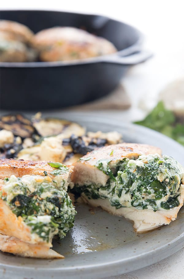 Stuffed chicken breast on a plate, cut open to see the spinach and three cheese filling.
