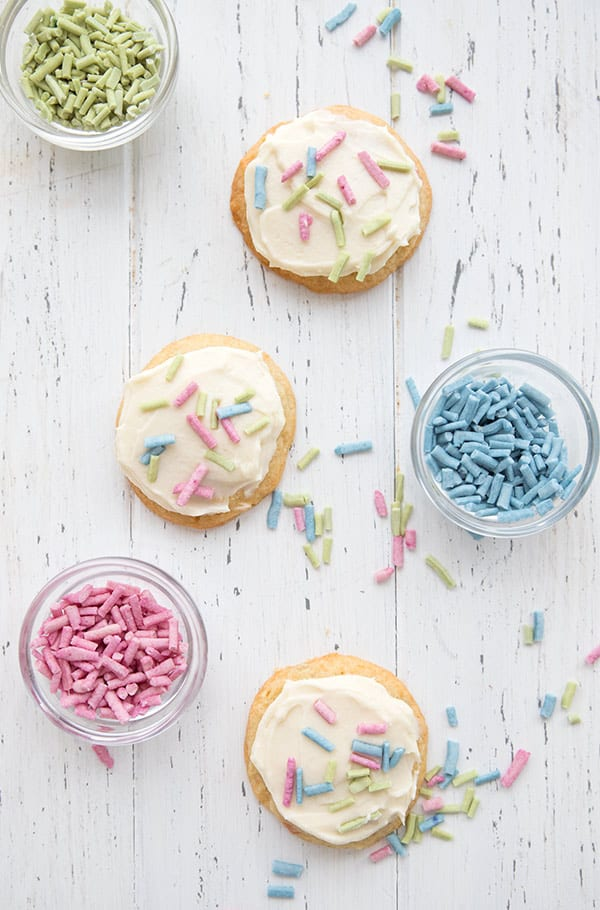 Top down photo of funfetti cookies with bowls of sprinkles