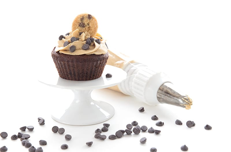 A chocolate cupcake with keto cookie dough frosting on a white cupcake stand