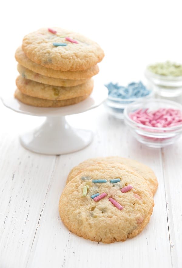 Tender soft almond flour sugar cookies on a white table with sugar-free sprinkles in the background