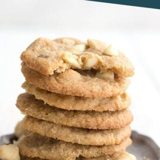 White chocolate chip macadamia nut cookies in a stack on a pewter plate