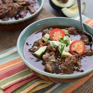A bowl of keto short rib chii topped with sour cream, cilantro, avocado and jalapeno