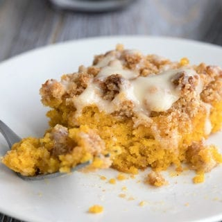 Close up shot of pumpkin coffee cake with a forkful taken out of it.