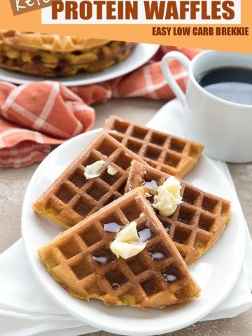 Keto pumpkin waffles on a white plate with butter on top