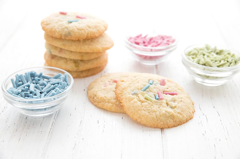 Funfetti cookies in a stack on a white table with little bowls of pastel sprinkles