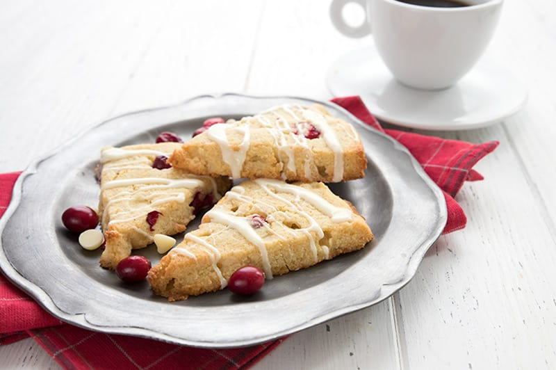 Three low carb cranberry scones on a pewter plate on top of a red plaid napkin