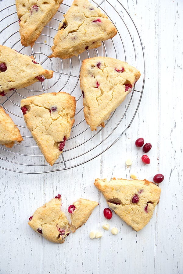 Top down photo of cranberry orange scones on a cooling rack over a white table.