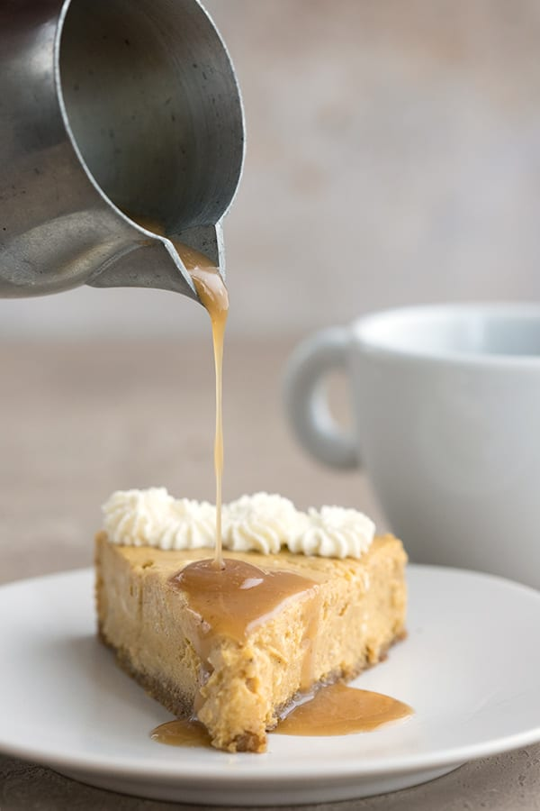 Pouring sugar-free caramel sauce over a slice of keto pumpkin cheesecake