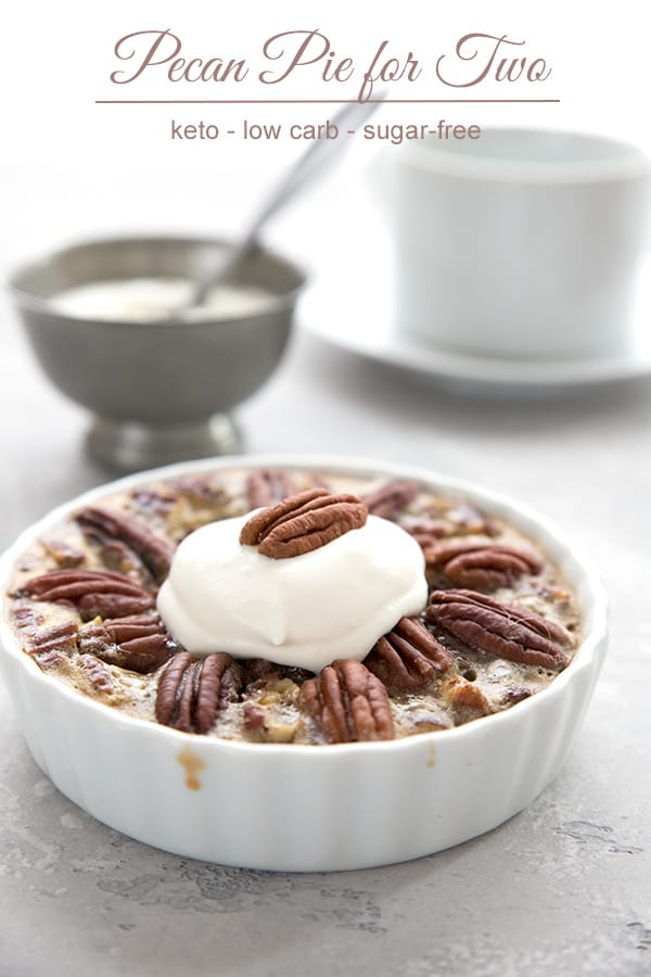 Mini pecan pie in a fluted white ramekin with whipped cream on top.