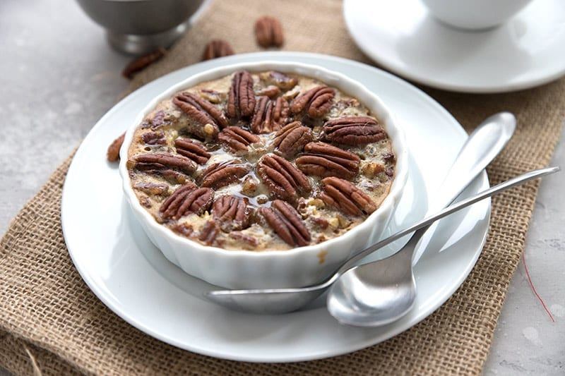 Easy pecan pie for two in a white ramekin on a white plate, with two spoons.