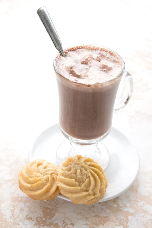 Keto hot chocolate in a glass mug with two low carb butter cookies on the plate.