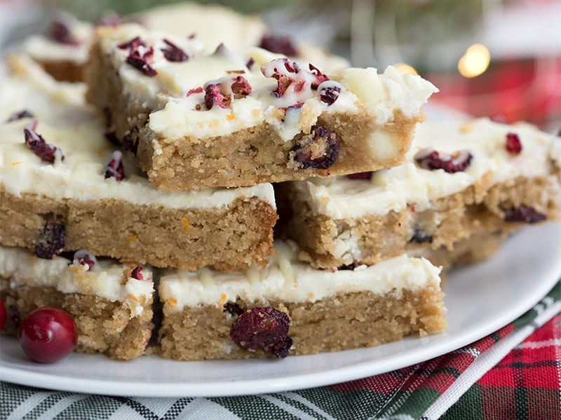Cranberry bliss bars in a stack on a holiday plaid napkin.