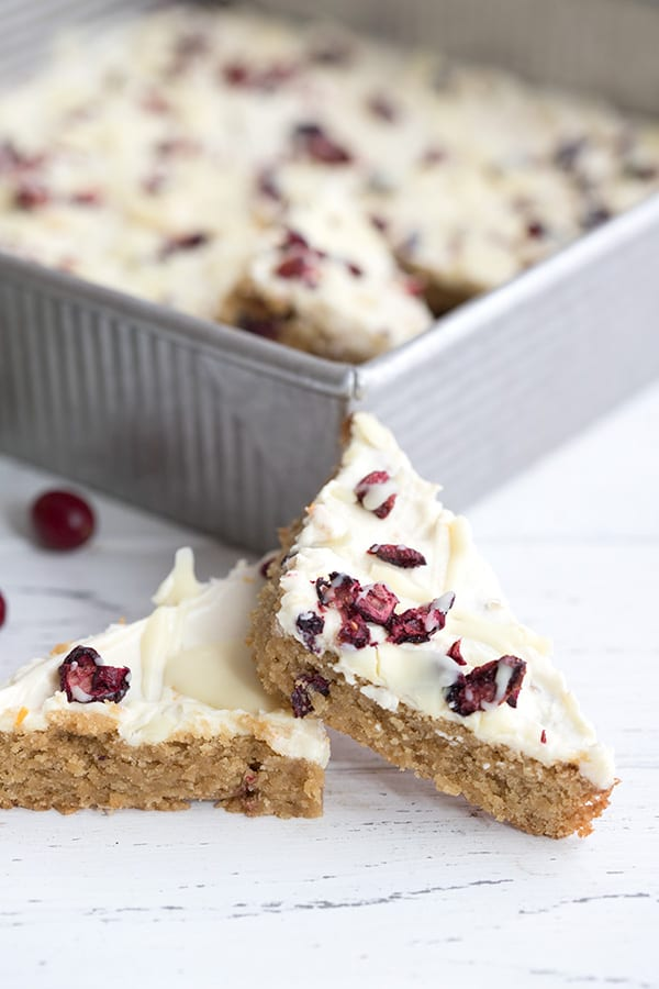 Close up of two keto cranberry bliss bars in front of the pan on a white table.