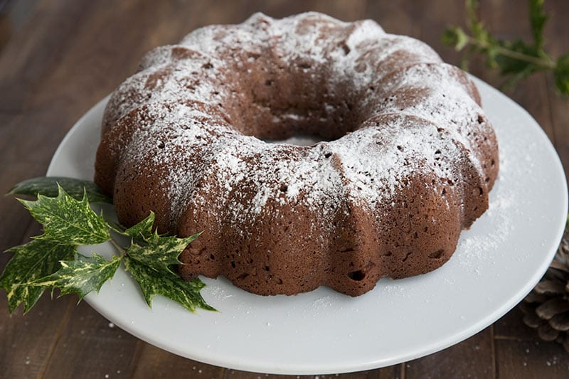 Gingerbread Cream Cheese Pound Cake on a white cake platter with holly around it.