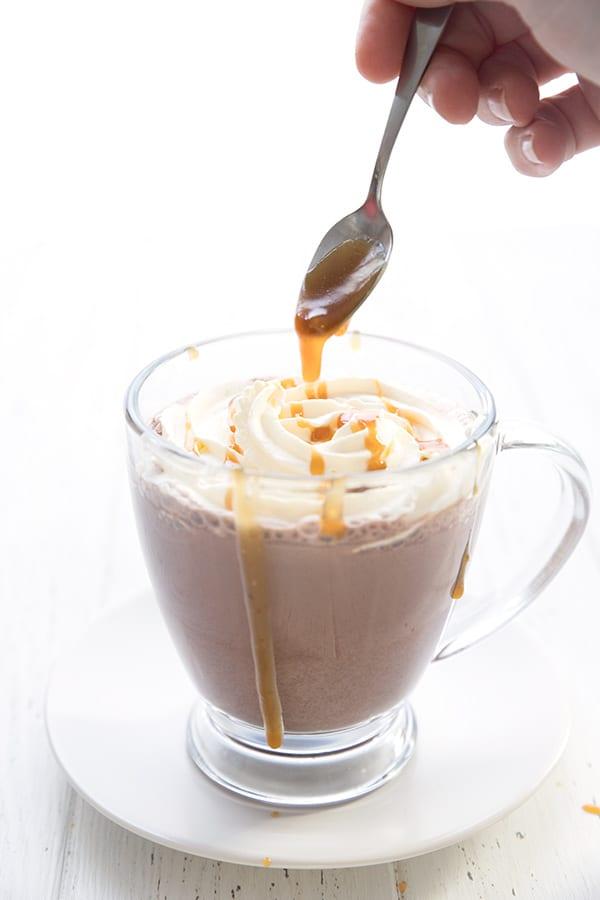 Drizzling sugar-free caramel sauce over a mug of keto hot chocolate.
