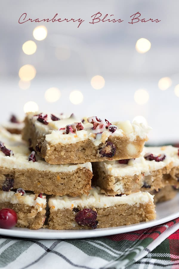 Keto copycat cranberry bliss bars on a white plate. Christmas lights in the background.
