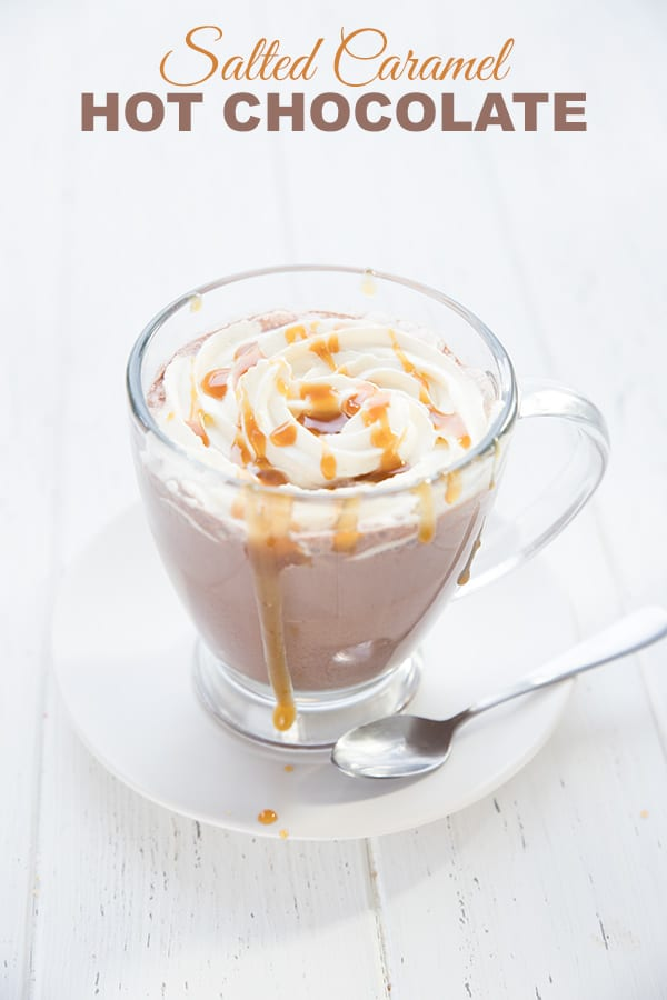 Keto salted caramel hot chocolate in a glass mug on a white table, with sugar-free caramel sauce drizzled overtop.