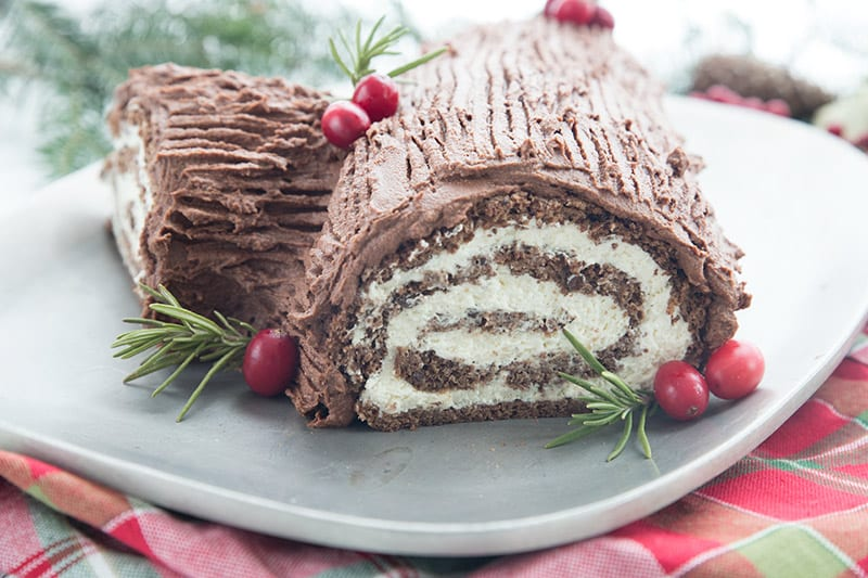 Keto yule log cake on a silver platter on top of a plaid red and green napkin.