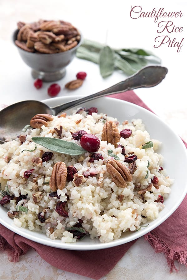 Cauliflower rice pilaf in a white bowl with cranberries, pecans, and sage