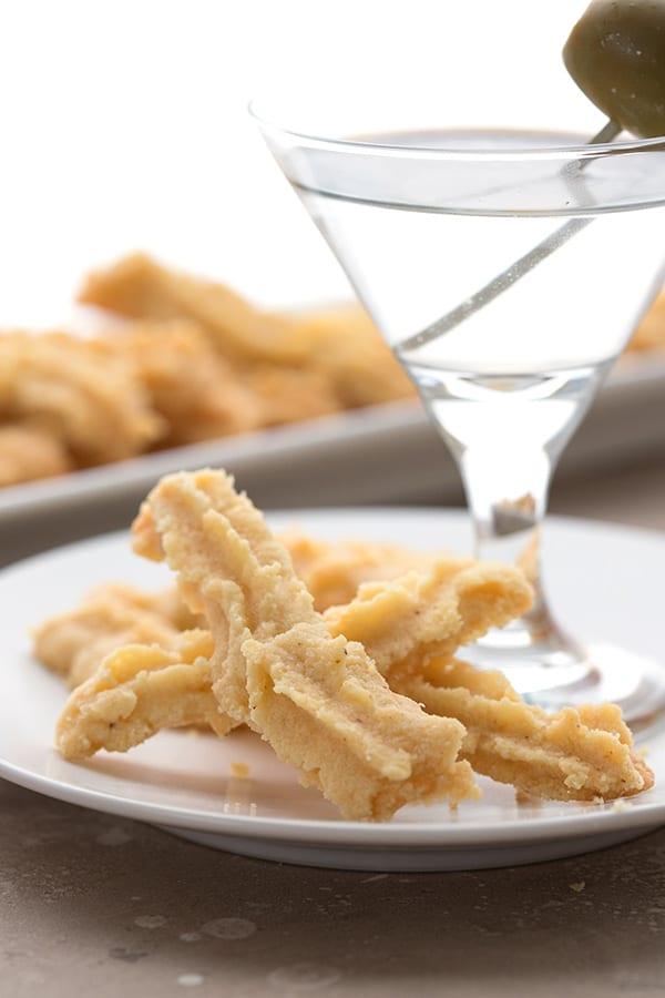 Keto cheese straws on a plate with a martini.