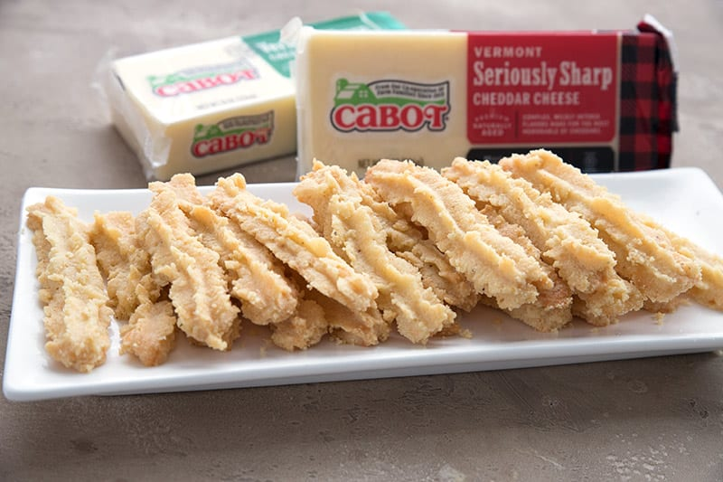 Low carb cheese straws in front of bricks of sharp cheddar cheese.