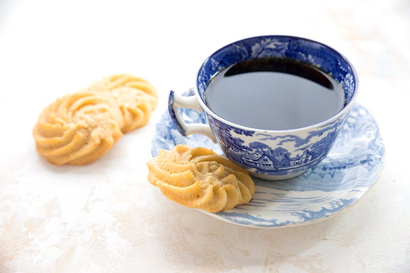 Danish butter cookies with a cup of tea in a blue willow pattern tea cup.