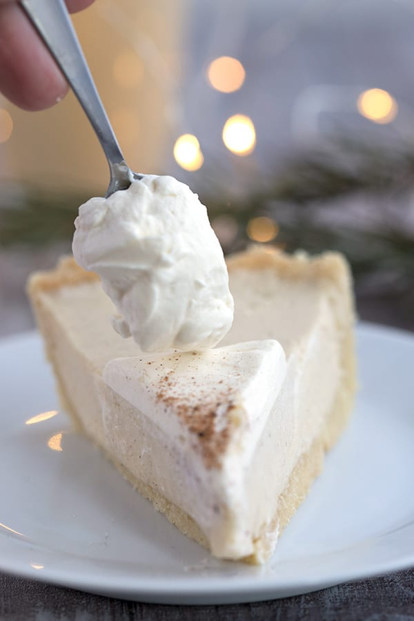 Whipped cream being dolloped over a piece of keto eggnog pie