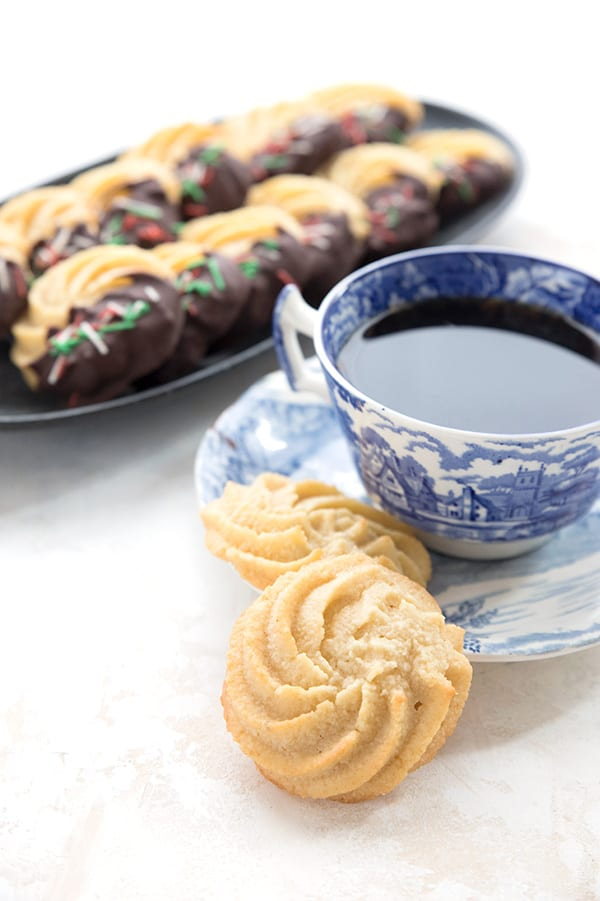 A cup of tea in a blue patterned tea cup with keto butter cookies.