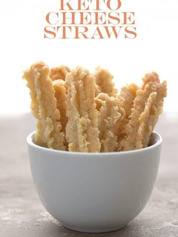 Keto cheese straws in a small white bowl on a brown table