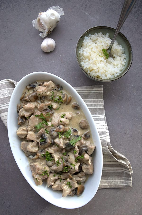 Top down photo of chicken and mushrooms in a white oval dish, with a bowl of cauliflower rice