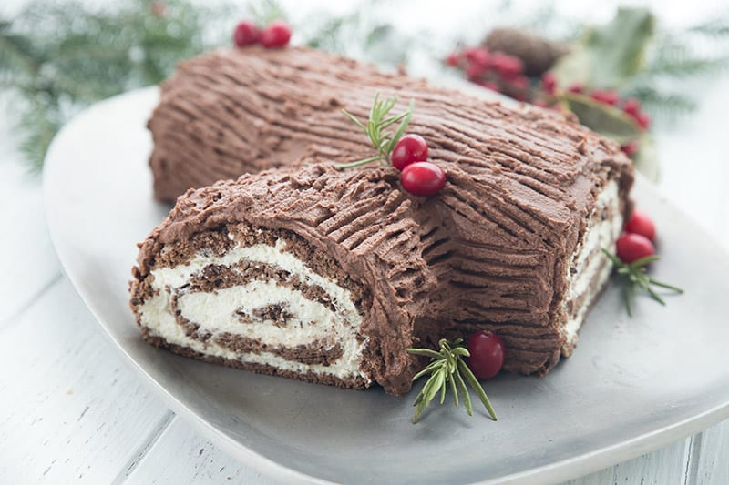A keto yule log cake on a silver platter with fresh cranberries and rosemary sprigs for garnish.
