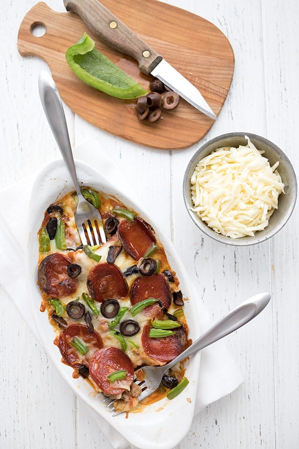 Top down photo of crustless pizza for two with a bowl of shredded cheese and a cutting board with green pepper and black olives on it.