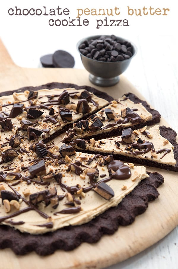 Keto chocolate peanut butter cookie pizza on a cutting board with chocolate chips and peanut butter cups in the background.