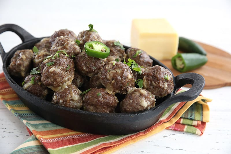 A dish of keto cheddar jalapeño meatballs with a block of cheddar and some jalapeño in behind.