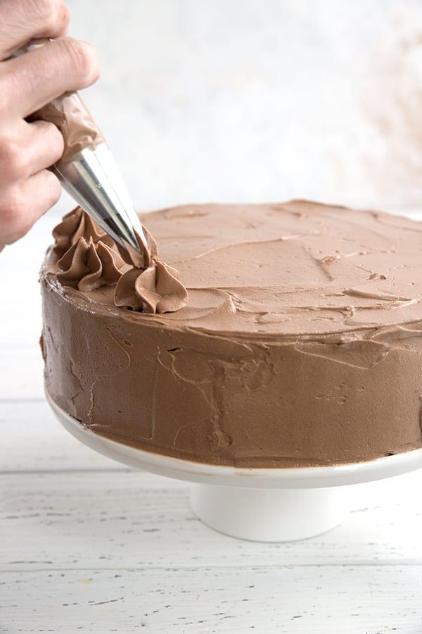 Piping sugar-free chocolate buttercream onto a keto birthday cake.